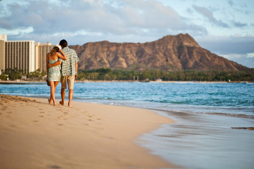 Couple walk along Waikiki with Leahi in back